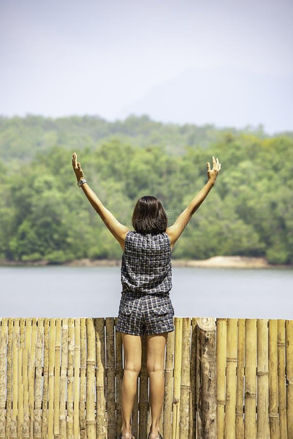 As mulheres aumentam suas montanhas e água do fundo dos braços no reservatório de Chakrabongse, Prachinburi em Tailândia fotografia de stock