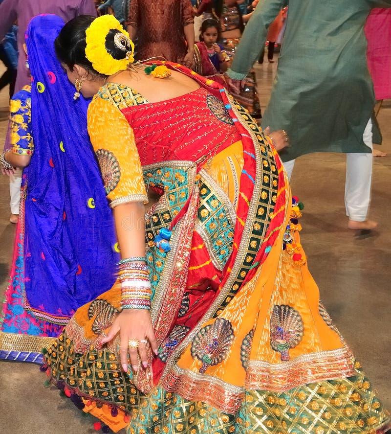 As mulheres bonitas estão dançando na ação Apreciando o festival hindu de vestir de Navratri Garba tradicional consuma fotos de stock