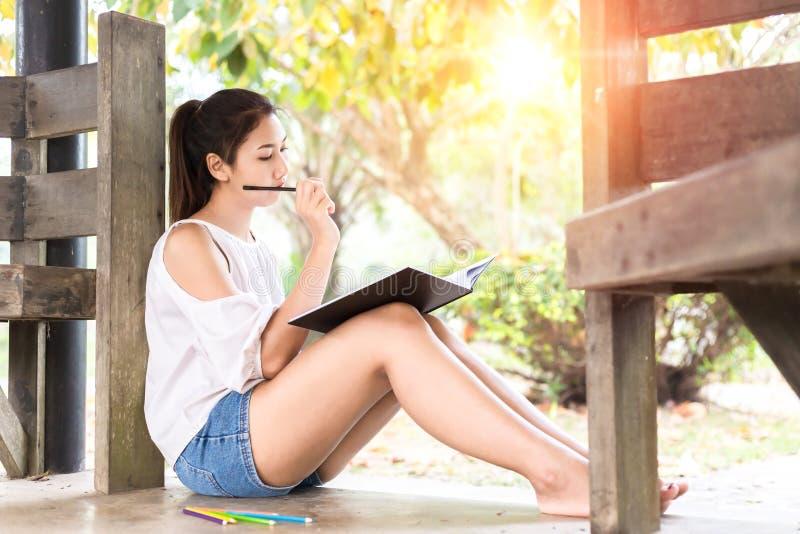 As mulheres bonitas que smilling e papel de escrita na terra no parque imagem de stock royalty free