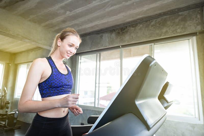 As mulheres brancas estão exercitando em máquinas do exercício Jovens que correm na escada rolante no gym Exercício caucasiano no foto de stock royalty free