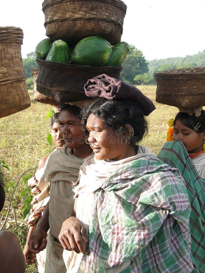 As mulheres carreg bens em suas cabeças imagens de stock