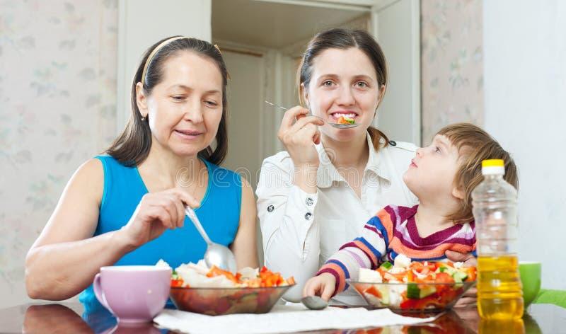 As mulheres com bebé comem a salada dos vegetais fotografia de stock royalty free