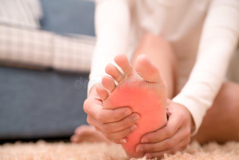 As mulheres da dor da lesão no calcanhar do pé tocam em seu pé conceito doloroso, dos cuidados médicos e da medicina fotografia de stock royalty free