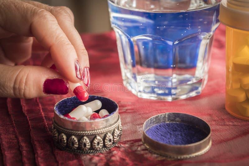 As mulheres da mão tomam as cápsulas vermelhas e brancas em uma caixinha de comprimidos foto de stock