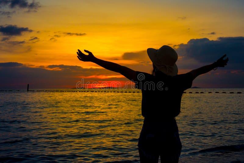 As mulheres da silhueta que vestem um chapéu estão apreciando um por do sol bonito o imagens de stock royalty free