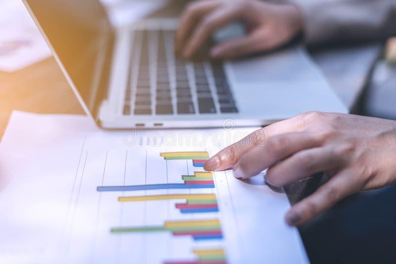 As mulheres de negócio apontam o dedo ao gráfico no papel e em um outro tipo da mão os dados no labtop, trabalhando fora do escri imagens de stock