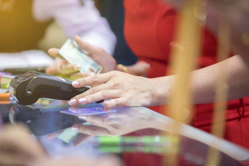 As mulheres de negócio asiáticas entregam usando o cartão de crédito que swiping a máquina para imagem de stock