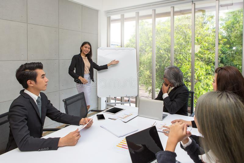 As mulheres de negócio estam presente na sala de reunião Funcionamento do negócio do grupo no escritório Os trabalhadores da equi fotografia de stock royalty free