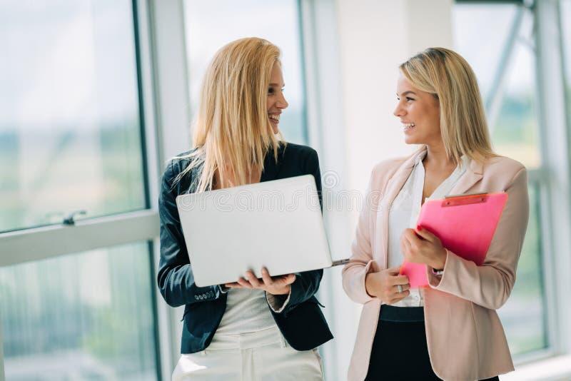 As mulheres de negócio olham e sorriem conversação com a tabuleta digital no escritório imagem de stock