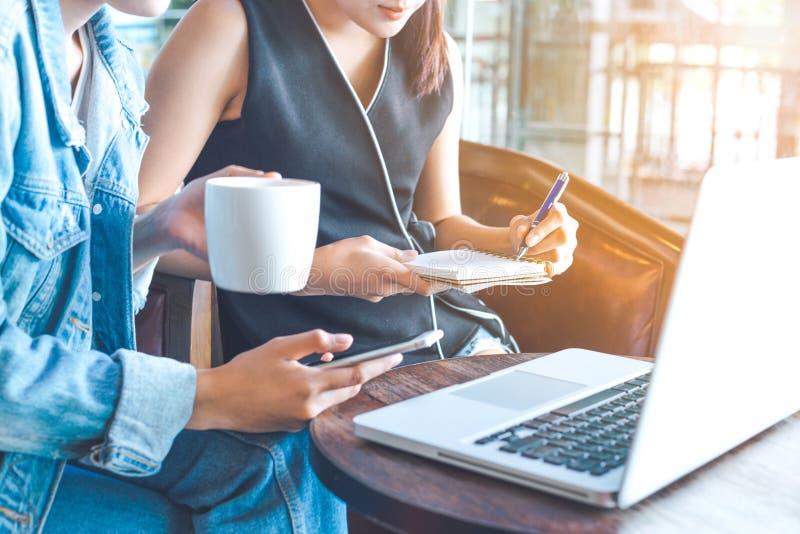 As mulheres de negócio trabalham em um computador e tomam notas em um caderno imagens de stock