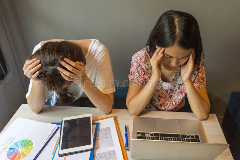 As mulheres de negócios frustradas sentem a dor de cabeça e cansaas com problema financeiro fotos de stock