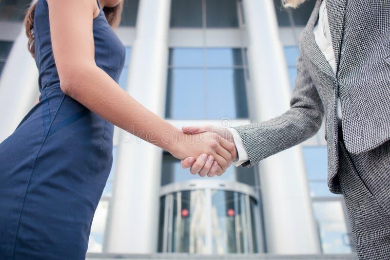 As mulheres de negócios novas bem sucedidas estão cumprimentando cada um fotografia de stock