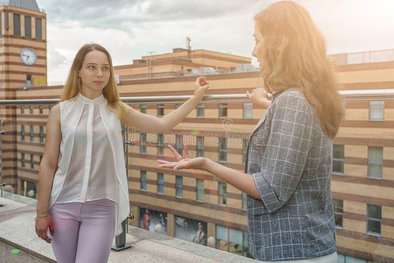 As mulheres de negócios têm discutem sobre o planeamento financeiro no terraço do corporaçõ de negócio fotografia de stock