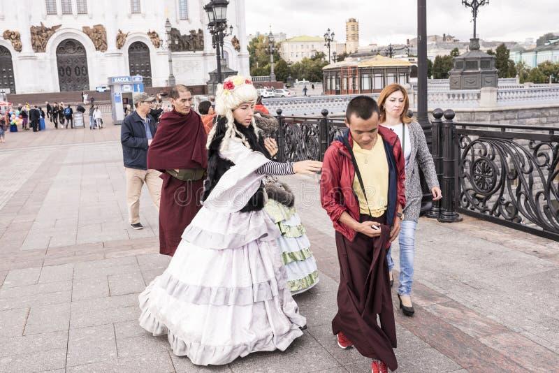 As mulheres de Roma em vestidos antigos fazem um tolo de monges tibetanas em t imagens de stock