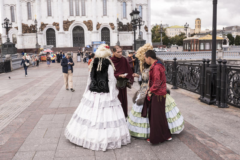 As mulheres de Roma em vestidos antigos fazem um tolo de monges tibetanas em t fotos de stock