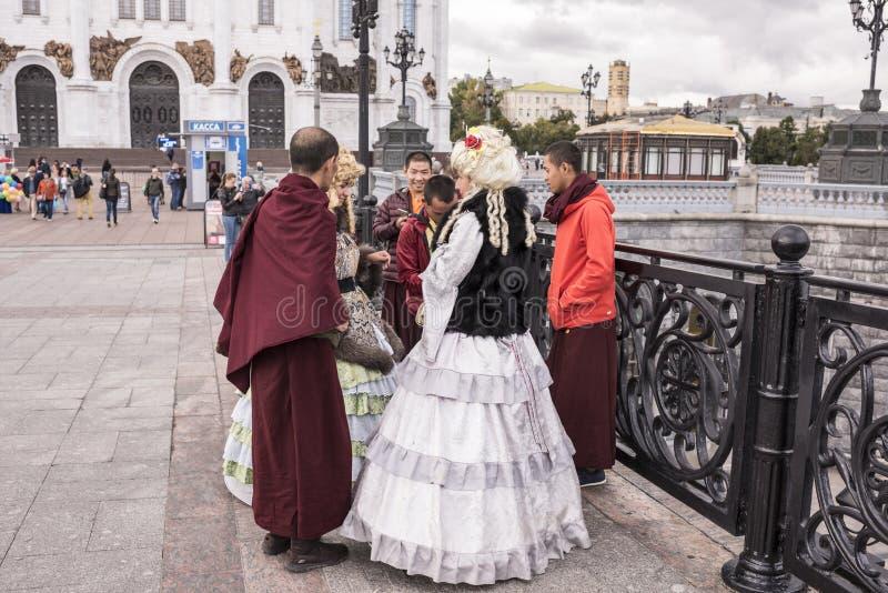 As mulheres de Roma em vestidos antigos fazem um tolo de monges tibetanas em t imagens de stock royalty free