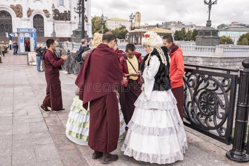 As mulheres de Roma em vestidos antigos fazem um tolo de monges tibetanas em t fotografia de stock royalty free