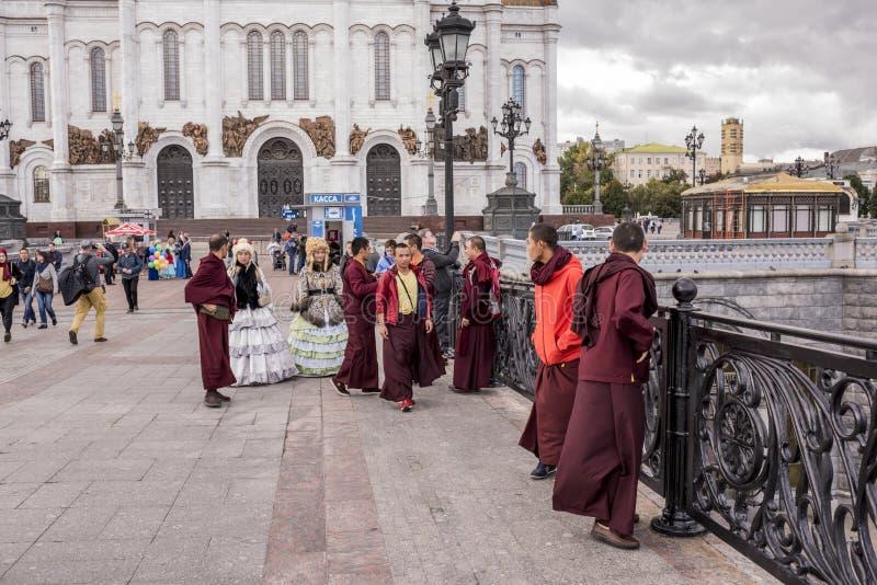 As mulheres de Roma em vestidos antigos fazem um tolo de monges tibetanas no th imagens de stock