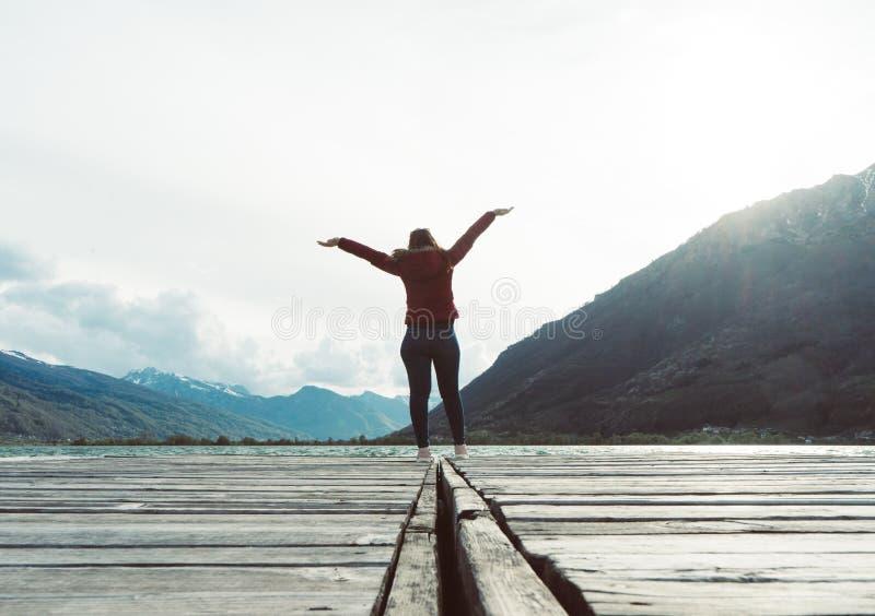 As mulheres de sorriso relaxam e posição vermelha vestindo do revestimento na ponte de madeira sobre o lago Curso e f?rias Concei imagens de stock