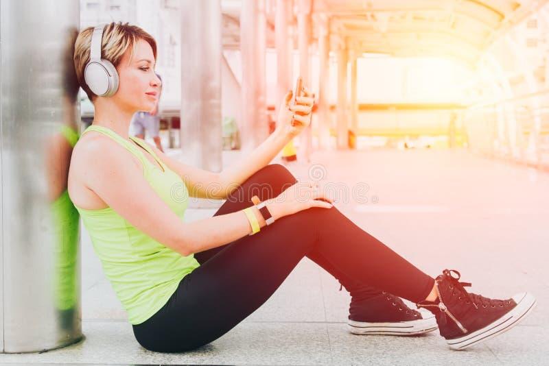 As mulheres do esporte relaxam para apreciar a música de escuta feliz e o sorriso imagens de stock