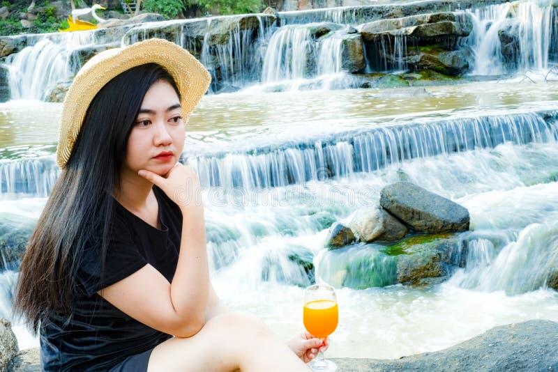 As mulheres do retrato entregam guardar o suco de laranja recentemente espremido no vidro com fundo da cachoeira fotografia de stock