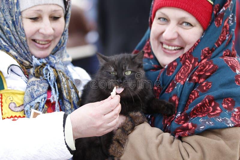 As mulheres do russo nos lenços alimentam o gato Festival nacional de Masl do russo fotos de stock