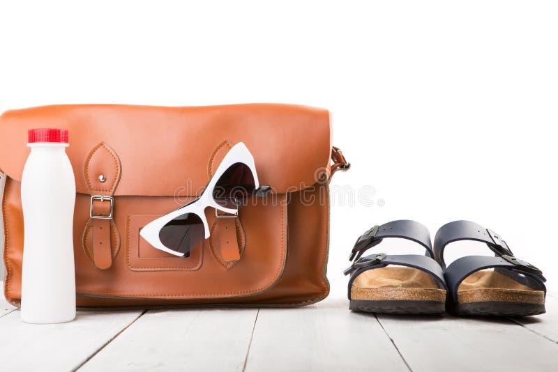as mulheres do verão ajustaram-se com saco de couro, sandálias, óculos de sol e bottl fotos de stock royalty free