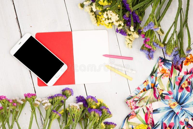 as mulheres do verão ajustaram-se com telefone esperto, vestido, flores coloridas, nota fotos de stock royalty free