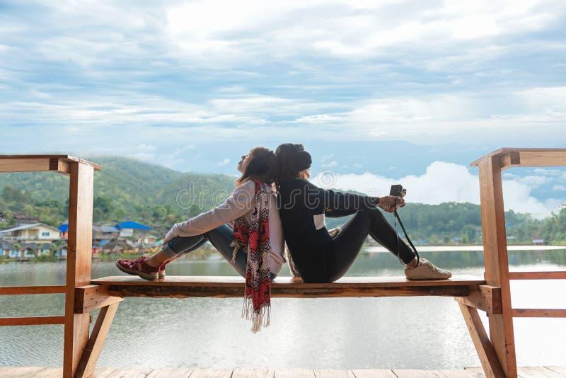 As mulheres do viajante dois estão situando no terraço no recurso sobre apreciam e relaxam com a natureza exterior do inverno imagem de stock