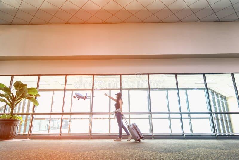 As mulheres do viajante planeiam e a trouxa vê o avião na janela de vidro do aeroporto, no saco da posse do turista da menina e n imagem de stock
