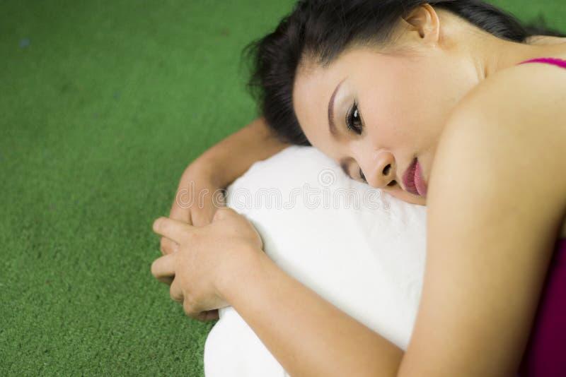 As mulheres dormem na grama verde, em uma mulher tailandesa bonita e sonhadora estabelecendo na grama verde, relaxando imagem de stock