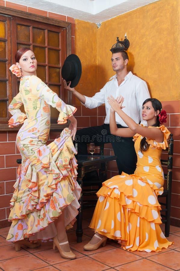 As mulheres e o homem em vestidos tradicionais do flamenco dançam durante Feria de abril em April Spain fotos de stock royalty free