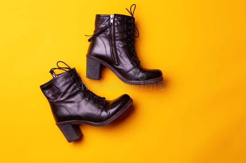 As mulheres elegantes enegrecem botas colocadas saltos Vista superior de botas pretas em um fundo amarelo fotos de stock