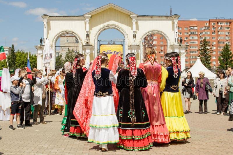 As mulheres em trajes nacionais dançam em um círculo, guardando as mãos foto de stock