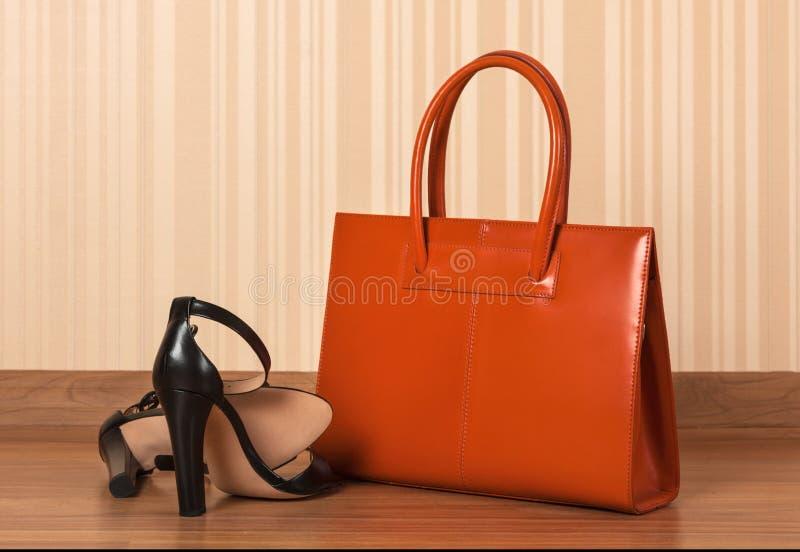 As mulheres enegrecem as sapatas de couro com saco de embreagem, no assoalho de madeira fotografia de stock royalty free