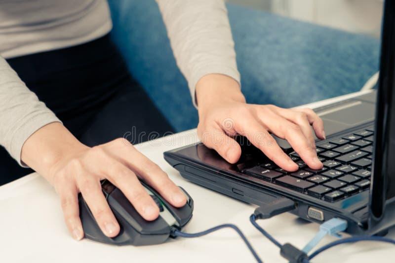 As mulheres entregam estão trabalhando no portátil e tocam no rato por outro lado fotos de stock royalty free