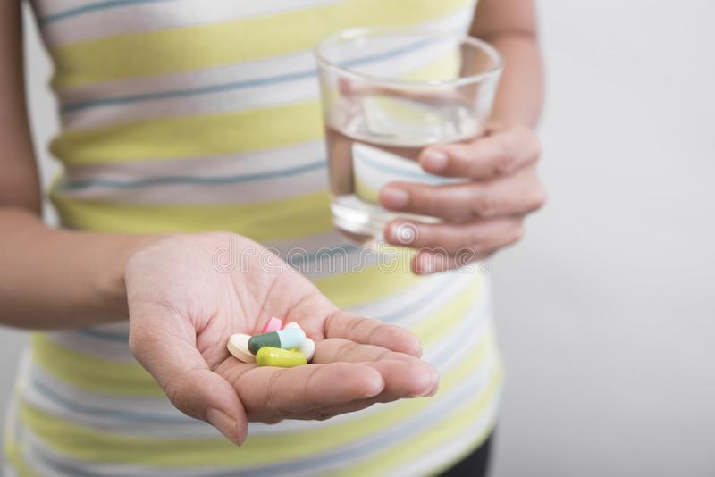 As mulheres entregam guardar o vidro da água estão tomando a medicina fotografia de stock royalty free
