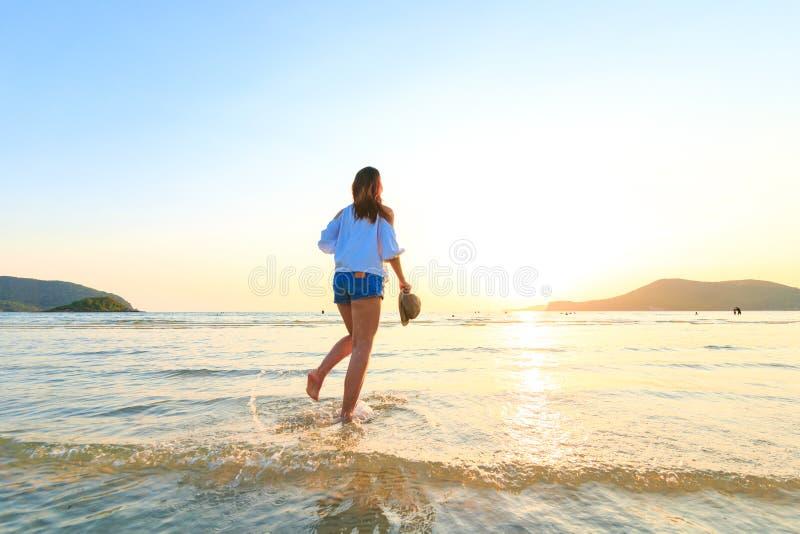 As mulheres estão e guardam o chapéu na praia entre o por do sol imagens de stock royalty free
