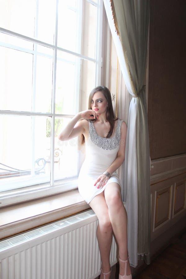 As mulheres estão próximo da janela na casa velha imagens de stock
