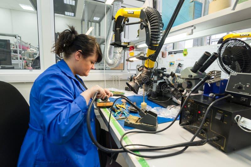 As mulheres fazem a solda dos componentes de rádio às placas eletrônicas Planta para a produção de equipamentos eletrônicos imagens de stock