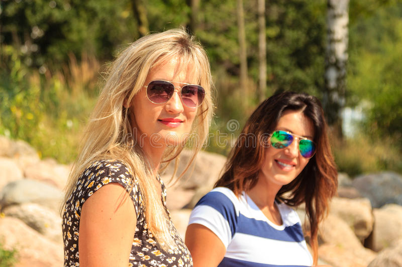 As mulheres felizes expõem ao sol bronzear-se e relaxar na praia foto de stock royalty free