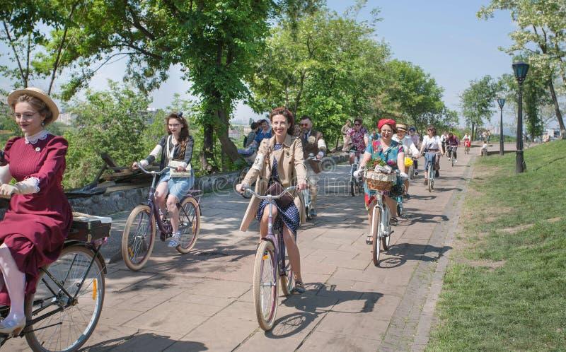 As mulheres felizes na forma velha denominam o ciclismo com a bicicleta do vintage no cruzeiro retro do festival da rua imagens de stock royalty free