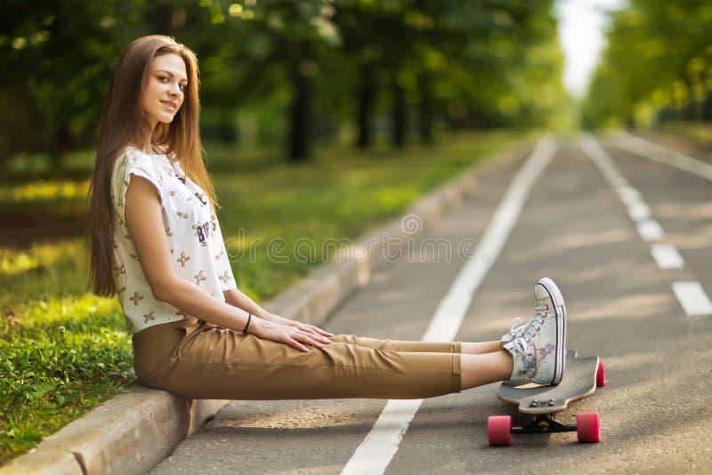 As mulheres felizes novas na moda que sentam-se em um parque puseram seus pés sobre o longboard e o sorriso skateboarding lifesty fotografia de stock