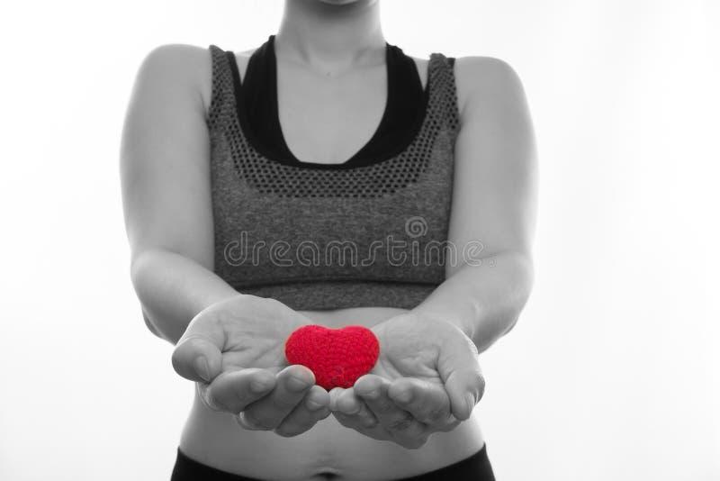 As mulheres gravidas asiáticas em sutiãs do esporte guardam o sinal vermelho da forma do coração sobre imagens de stock