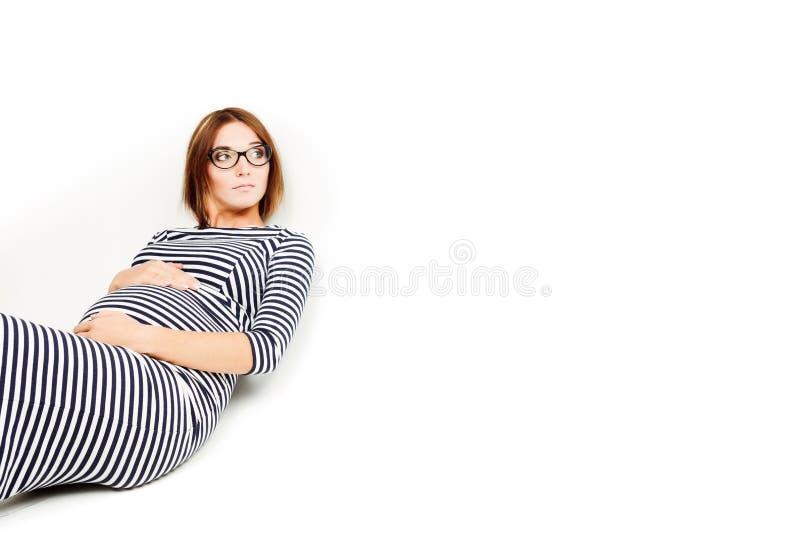 As mulheres gravidas felizes sentam-se no assoalho e os toques incham-se foto de stock