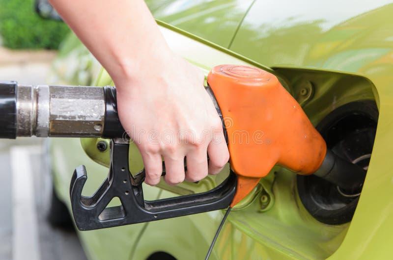 As mulheres guardam o bocal de combustível para adicionar o combustível no carro no posto de gasolina fotos de stock