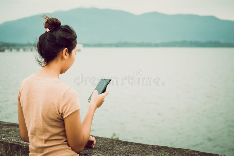 As mulheres guardam o telefone celular para a mensagem e o e-mail da verificação imagem de stock