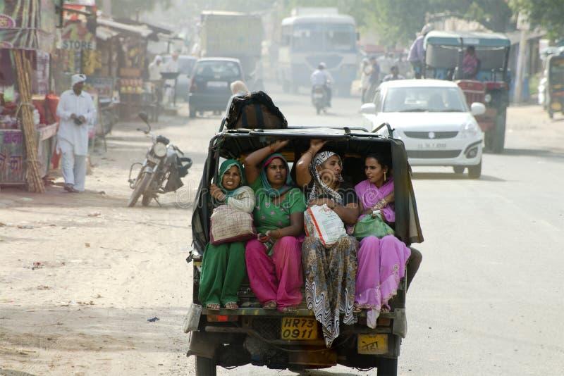 As mulheres hindu na Índia montam um táxi de três rodas fotografia de stock