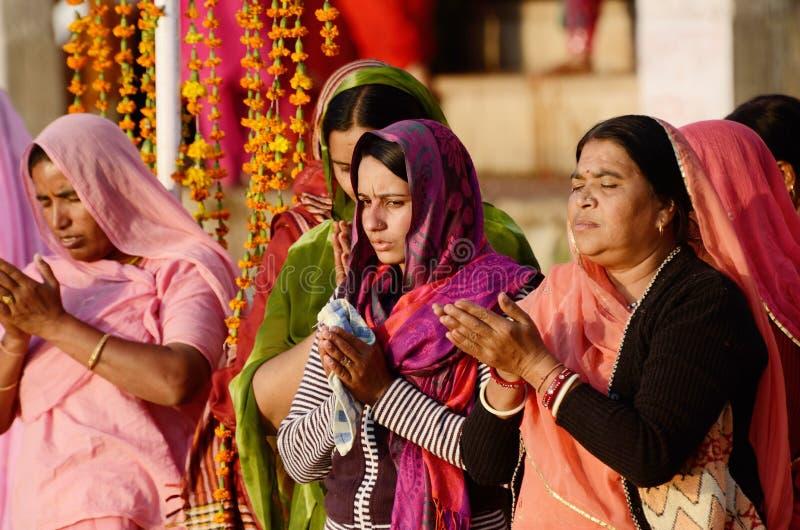 As mulheres hindu superiores e novas no sari colorido executam o puja no lago santamente Sarovar, Índia fotografia de stock royalty free