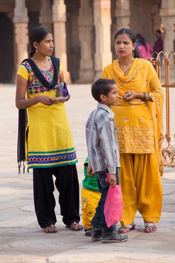 As mulheres indianas com as crianças que estão no pátio de Quwwat-Ul-estão fotografia de stock royalty free